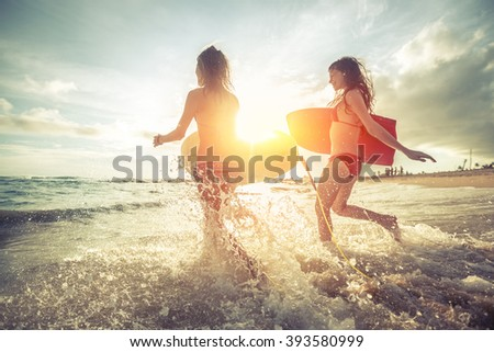 Two young women running into the sea with surf boards