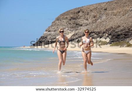 Two young women running on the beach, Fuerteventura, Spain - stock photo