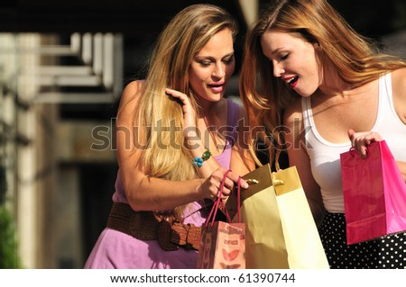 two young women sharing their new purchases with each other - stock photo