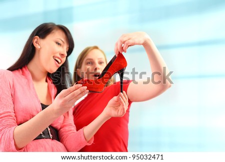 Two young women shopping for shoes - stock photo