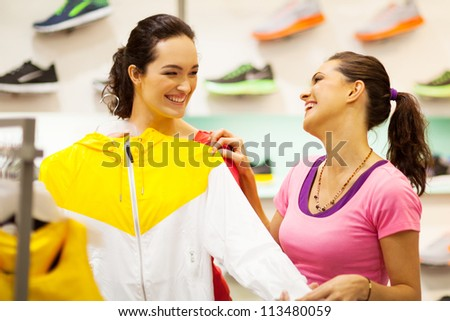 two young women shopping for sportswear in mall - stock photo