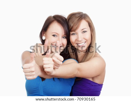 two young women showing thumbs up, smiling - isolated on white - stock photo