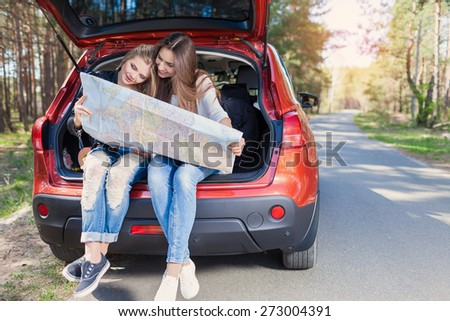 Two young women sitting in a trunk of car look at road map - stock photo