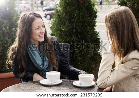 Two young women sitting in cafe and chatting outdoors. - stock photo