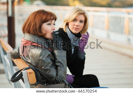 Two young women sitting on a bench. - stock photo