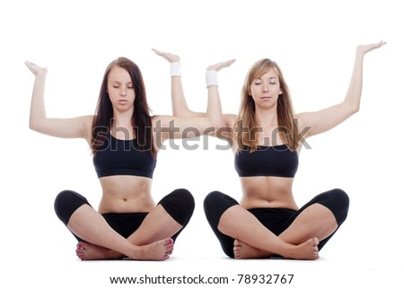 two young women sitting on the floor exercising yoga - isolated on white - stock photo