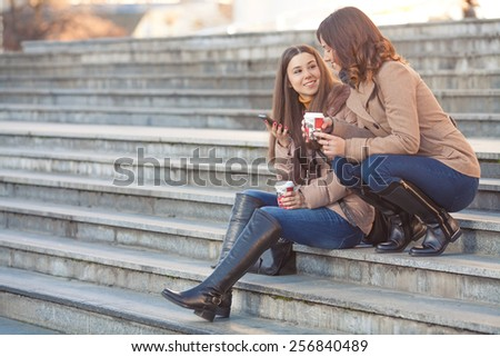 Two young women sitting on the stairs in front of the office building - stock photo
