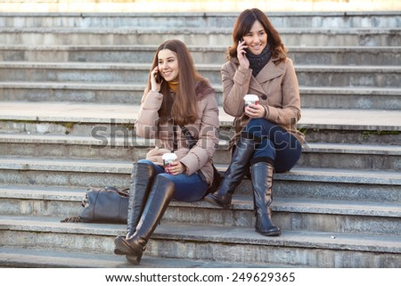 Two young women sitting on the stairs talking on their mobile phones - stock photo
