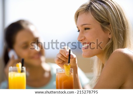 Two young women sitting with cocktails outdoors, smiling - stock photo