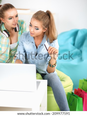 Two young women sitting with laptop  and credit cart at home - stock photo