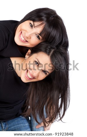Two young women smiling and piggyback - stock photo