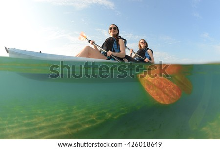 Two young women smiling in blue kayak in Atlantic Ocean off of the coast of Florida - stock photo