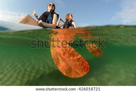 Two young women smiling in kayak off of the coast of Florida - stock photo