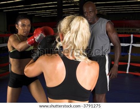 Two young women sparring in a boxing ring while their trainer looks on - stock photo