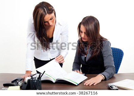Two young Women standing behind a workplace - stock photo