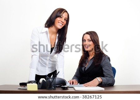 Two young Women standing behind a workplace