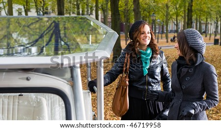 Two young women standing next to a  solar powered tuc tuc - stock photo