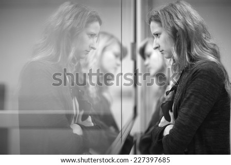 Two young women standing, reflection on the mirror, monochrome - stock photo