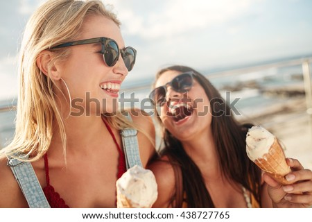 Two young women standing together laughing and eating ice cream. Happy young female friends with icecream enjoying together on a summer day. - stock photo