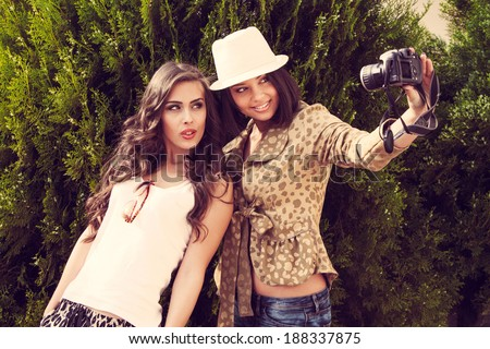 two young women take photo with camera outdoor shot - stock photo