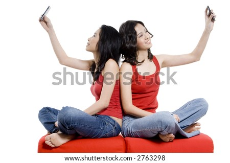 Two young women take their pictures using the digital cameras on their mobile phones