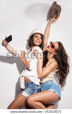 two young women taking picture of them selfs with mobile - stock photo