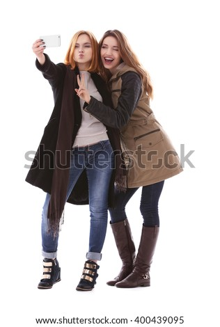 Two young women taking selfie in their winter clothes isolated on white - stock photo
