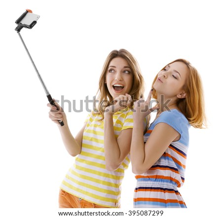 Two young women taking selfie with mobile phone isolated on white - stock photo