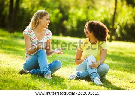 Two young women talking in park - stock photo