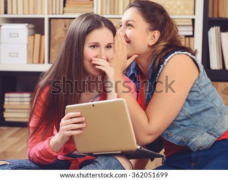Two young women talking in the library - stock photo
