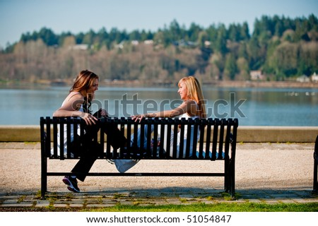 Two young women talking on a bench by a lake