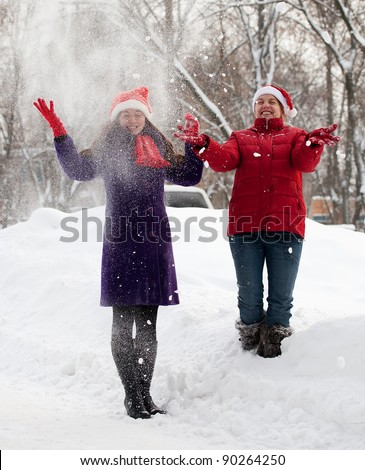 Two  young women throwing snow in the air - stock photo