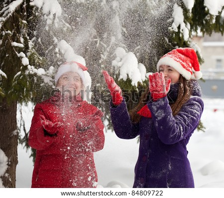 Two  young women throwing snow  in the air in park - stock photo