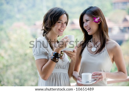 Two young women together outside having coffee - stock photo