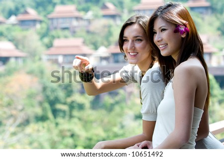 Two young women together outside on a balcony - stock photo