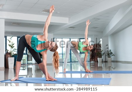 Two young women training in yoga asana in the gym - stock photo