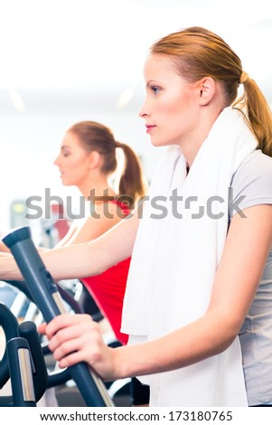 Two young women training on cardio or endurance machine in gym sport center