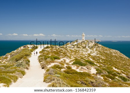 Two young women walk towards the lighthouse at Cape Spencer, South Australia, perched high above the ocean. - stock photo