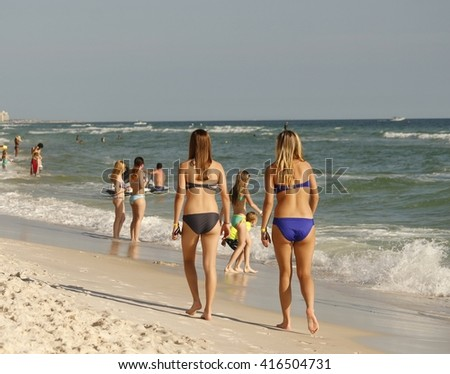 Two young women walking along a sandy beach in Florida; people in the background - stock photo