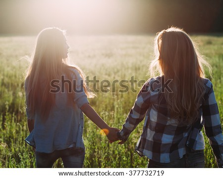 Two young women walking at sunset.  Back view. Best friends - stock photo