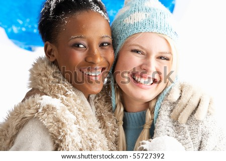 Two Young Women Wearing Warm Winter Clothes Holding Snowball In Studio - stock photo