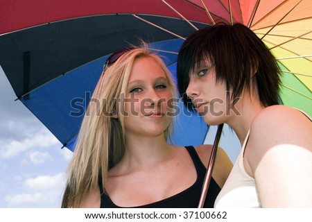 two young women with a rainbow colored parasol