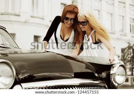 Two young women with a road map on the retro car - stock photo