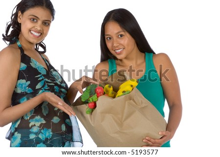 Two young women with bag of fresh vegetables - stock photo