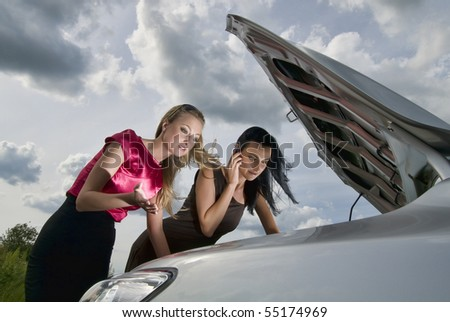 Two young women with broken car - stock photo