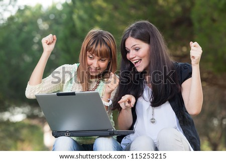 Two Young Women with Computer at Park - stock photo