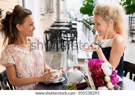 Two young women with great smile and hairstyle sitting at a bar, drinking tea and coffee. - stock photo