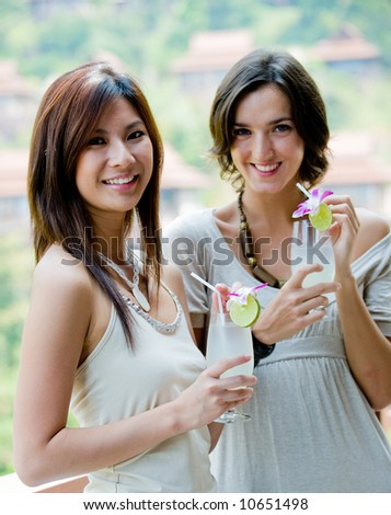 Two young women with lime drinks on vacation - stock photo