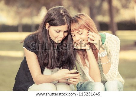 Two Young Women with Mobile Phone - stock photo