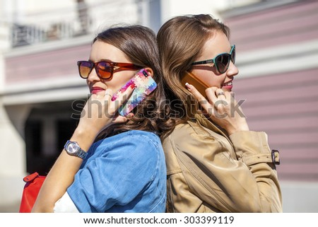 Two Young Women with Mobile Phone on spring street background  - stock photo